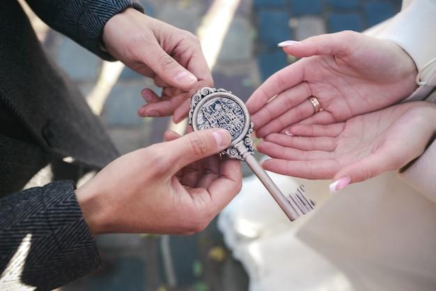 신랑과 신부의 손에 열쇠가 달린 자물쇠 무료 사진