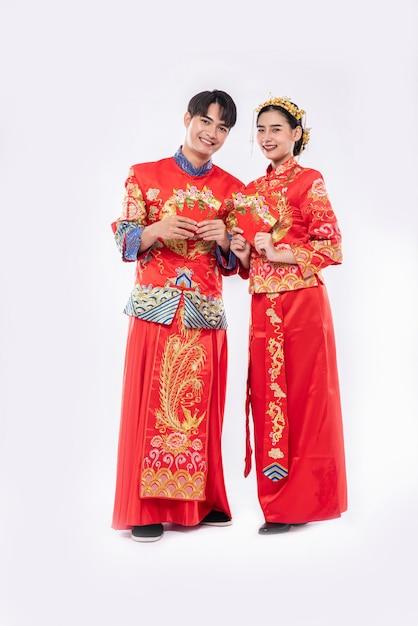 男性と女性は伝統的な日に家族への赤い贈り物のお金を準備してチャイナドレスを着ています 無料写真