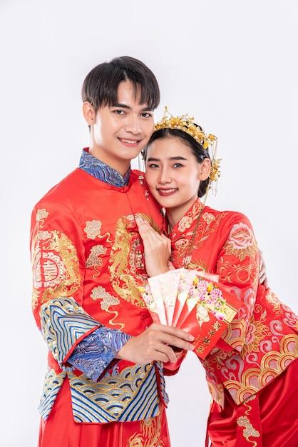 男性と女性は伝統的な日に家族からの赤い贈り物のお金を見せてチャイナドレスを着ています 無料写真