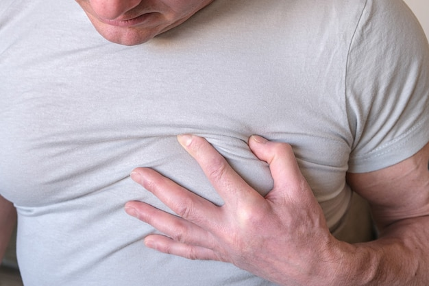 Мужчина схватился за грудь. стенокардия сердечного приступа на белом Premium Фотографии