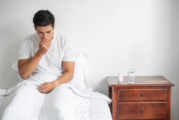 Мужчина закашлялся, зажал рот рукой и сел на кровать. Бесплатные Фотографии