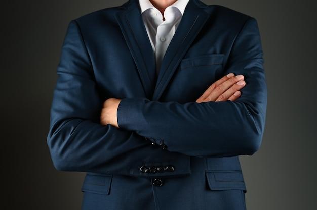 スーツを着た男は腕を組んだ。黒い空間でスーツを着た男。コンセプト:ビジネスでの建設。 Premium写真