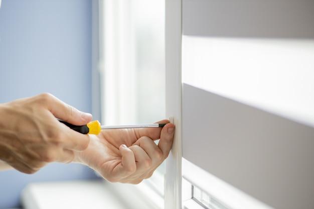 男はプラスチックの窓を修理しています。 Premium写真