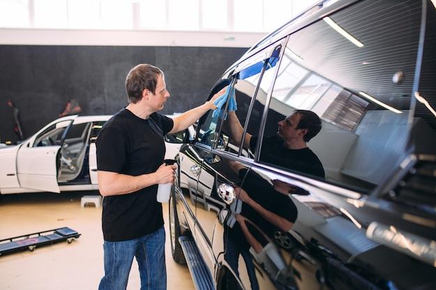男は見事な車の布で拭きます。 Premium写真