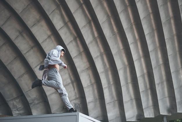 男は屋外でパルクール、極端なアクロバットを練習しています。 無料写真