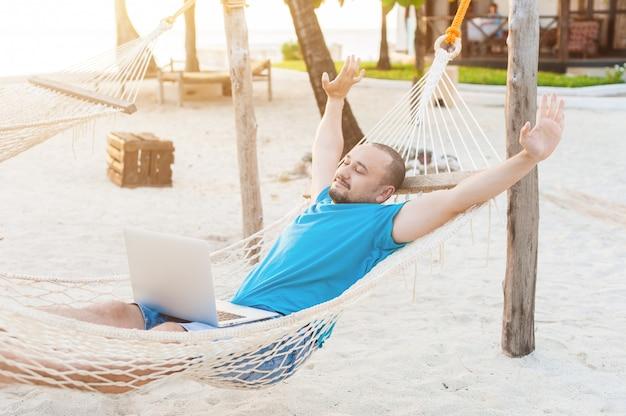 Мужчина довольно растягивается, лежа в гамаке с ноутбуком. Premium Фотографии