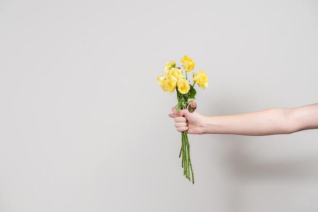 男の手はしおれた花の花束を差し出し、イチジクを示しています。分離の概念。テキストの場所のあるレイアウト Premium写真
