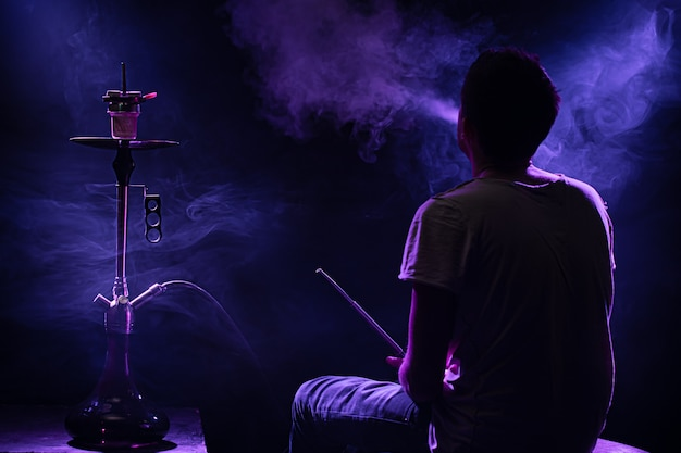 Мужчина курит классический кальян. красивые цветные лучи света и дыма. понятие о курении кальяна. Бесплатные Фотографии