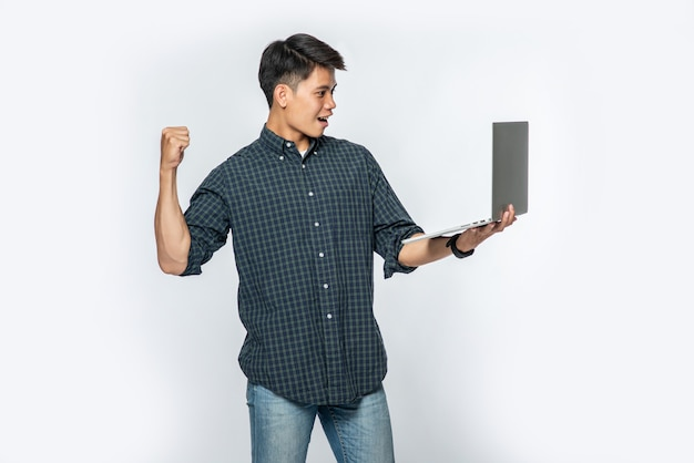 На мужчине была белая рубашка и темные штаны, он держал ноутбук и делал вид, что радуется. Бесплатные Фотографии