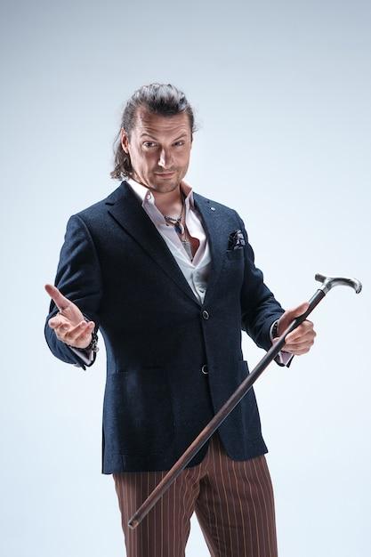 Зрелый бородатый мужчина в костюме держит трость. Бесплатные Фотографии