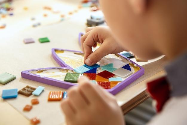 子供のためのモザイクパズルアート、子供たちの創造的なゲーム。手はテーブルでモザイクを遊んでいます。カラフルなマルチカラーのディテールをクローズアップ。創造性、子供の発達と学習のコンセプト 無料写真