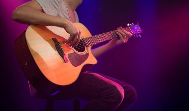 Музыкант играет на акустической гитаре. Бесплатные Фотографии