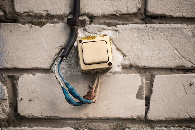 レンガの壁の古いスイッチは、青いテープをねじっていました。 無料写真