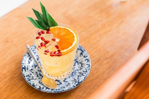 スライスしたオレンジとザクロの果肉をグラスに混ぜたオレンジのフルーティーなカクテル。バナナの葉で飾られました。 Premium写真