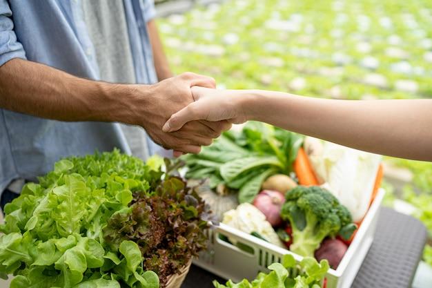 Владелец фермы по выращиванию органических овощей рассказал покупателям об экспортном бизнесе. рукопожатие при успешном разговоре. Premium Фотографии