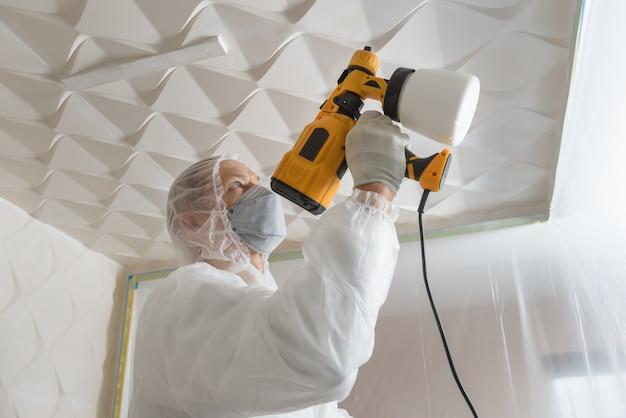Художник красит 3d потолок с помощью краскопульта. Premium Фотографии