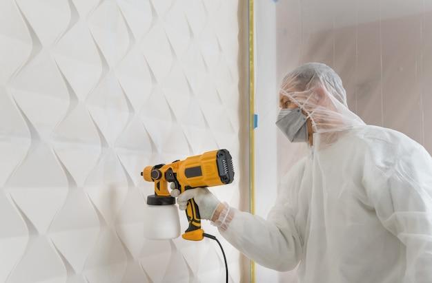 Художник красит 3d стену из краскопульта. Premium Фотографии