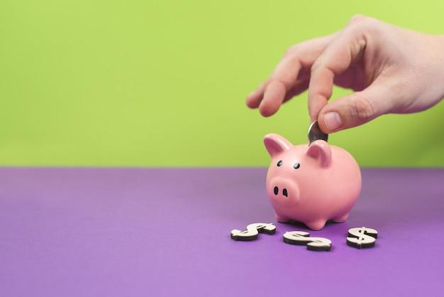 貯金箱は紫と緑のテーブルにピンクです Premium写真