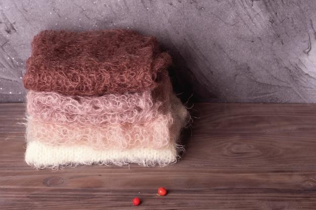 Куча пастельных шерстяных шарфов на деревянном фоне Premium Фотографии