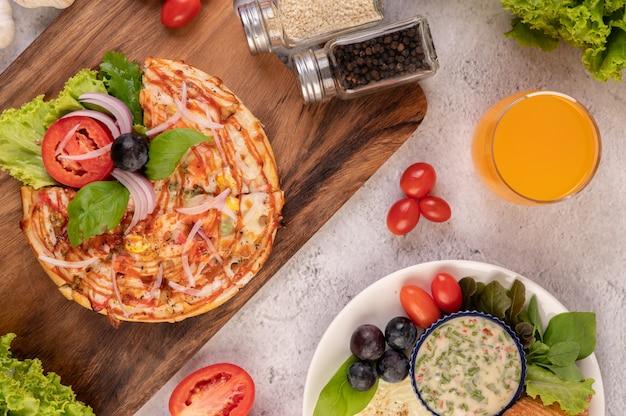 ピザは、赤玉ねぎ、黒ブドウ、トマト、レタスをトッピングした木製トレイにあります。 無料写真