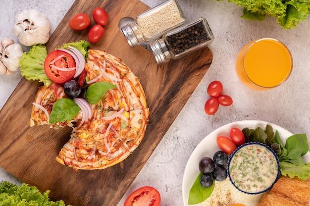 Пицца находится в деревянном подносе с красным луком, черным виноградом, помидорами и салатом. Бесплатные Фотографии