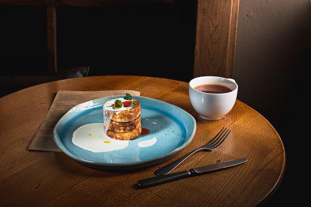 Тарелка с вкусными блинами на деревянный стол Бесплатные Фотографии