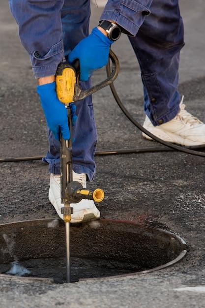 配管工は下水道の問題を解決する準備をしています。トラブルシューティングの修理作業。閉じる。 Premium写真