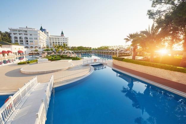 人気のリゾート、アマラドルチェヴィータラグジュアリーホテル。トルコの海岸沿いのプールとウォーターパーク、レクリエーションエリアが夕日にあります。ケメロボ・ケメル。 無料写真