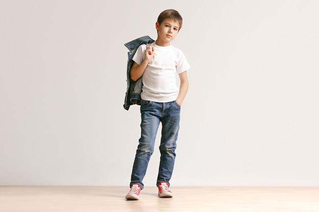 스튜디오에서 카메라를보고 세련된 청바지 옷에 귀여운 어린 소년의 초상화 무료 사진