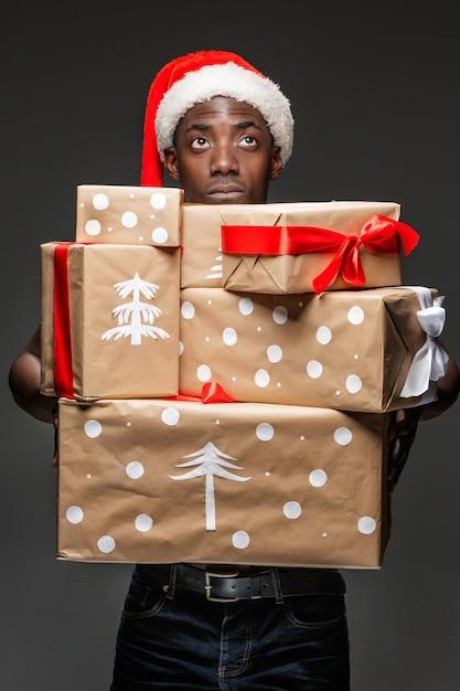 ハンサムな若い黒人アフリカの肖像画は、暗い背景に贈り物をサンタ帽子の男を驚かせた。肯定的な人間の感情とメリークリスマスのコンセプト 無料写真