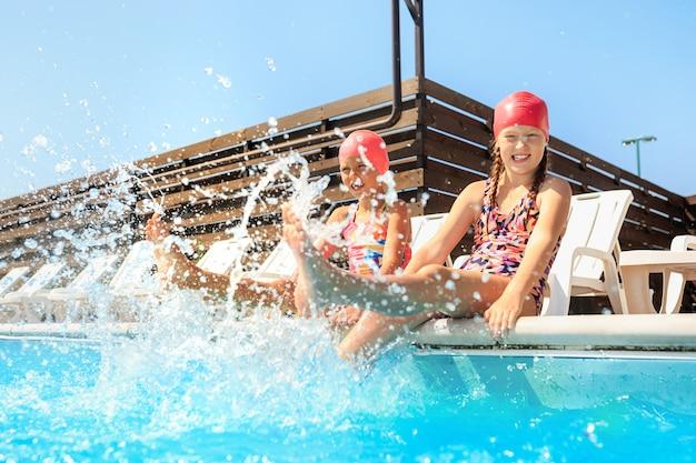 Портрет счастливых улыбающихся красивых девочек-подростков в бассейне. Бесплатные Фотографии
