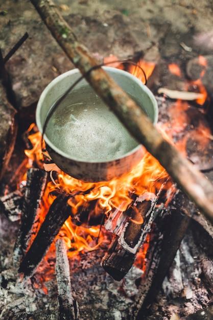 Ночью возле палатки в лесу горит котелок. красивый костер в туристическом лагере в дикой природе. Premium Фотографии