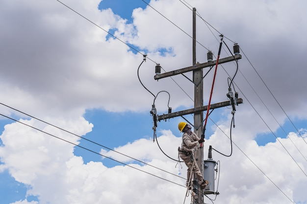 Линии электропередач используют зажимную рукоятку (изолированный инструмент) для замыкания трансформатора на линиях электропередачи высокого напряжения. Premium Фотографии