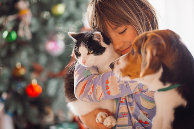 Симпатичная девушка, укрывающая кошку и собаку Бесплатные Фотографии