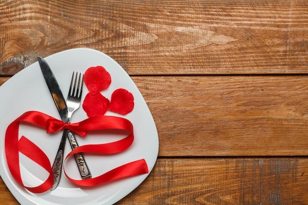 나무 배경에 접시에 빨간 리본입니다. 발렌타인 데이 개념. 무료 사진