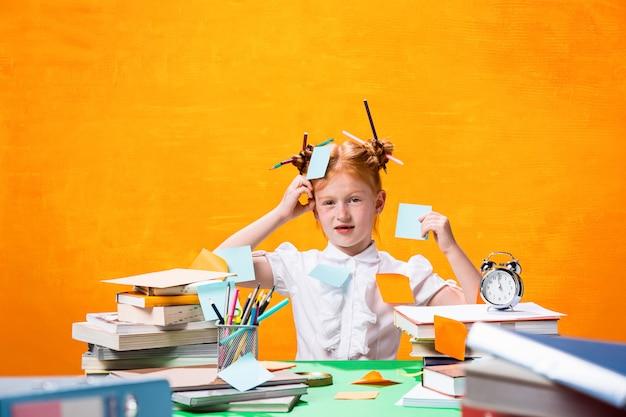 Рыжая девочка-подросток с множеством книг дома. студийный снимок Бесплатные Фотографии