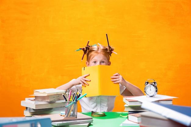 家にたくさんの本を持つ赤毛の十代の少女。スタジオ撮影 無料写真