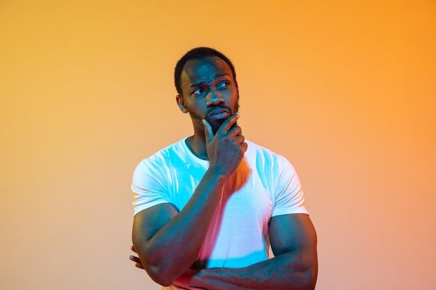 Ретро волна волны или synth развевает портрет молодого счастливого серьезного африканского человека на студии. Бесплатные Фотографии