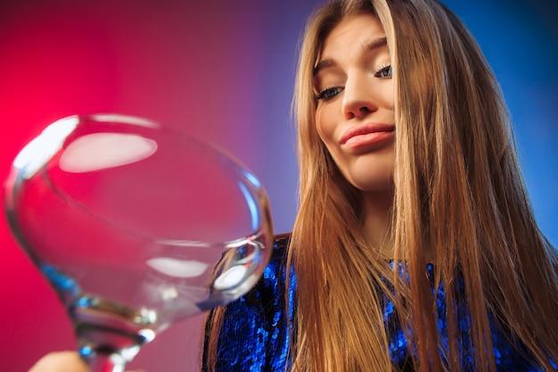 Грустная молодая женщина в партийной одежде позирует с бокалом вина. Бесплатные Фотографии