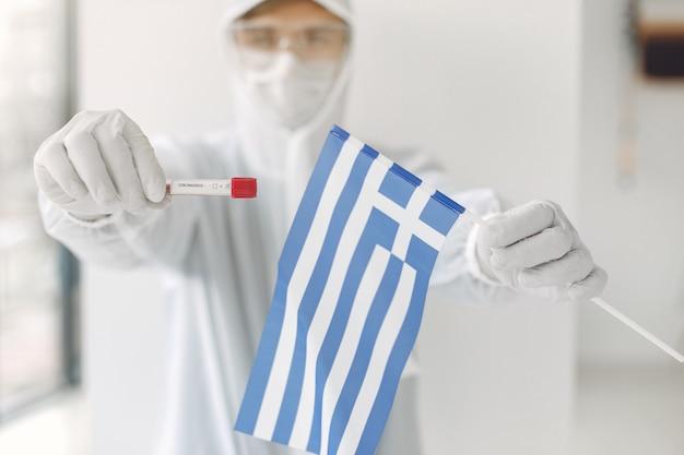 コロナウイルスのサンプルとギリシャ国旗を持つつなぎ服の科学者 無料写真