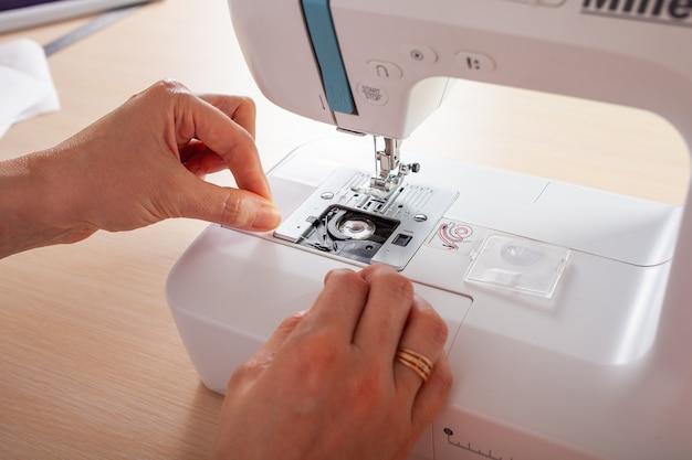 Мастерица заправляет нитью в нижнюю катушку автоматической швейной машины. Premium Фотографии
