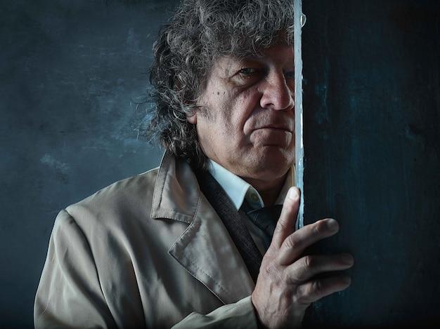 Старший мужчина, как детектив или босс мафии на сером Бесплатные Фотографии