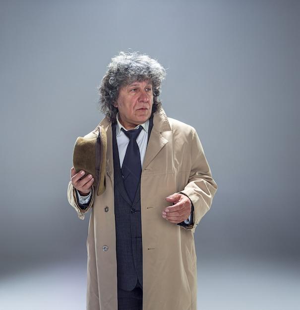 Старший мужчина в плаще, как детектив или босс мафии. Бесплатные Фотографии