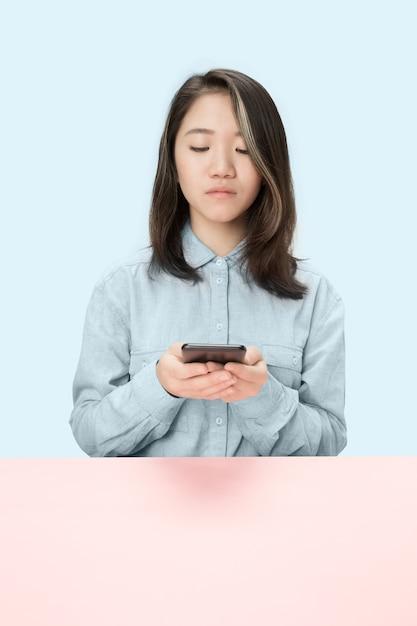 青い背景に座って電話を見ている真面目なビジネス女性。 無料写真