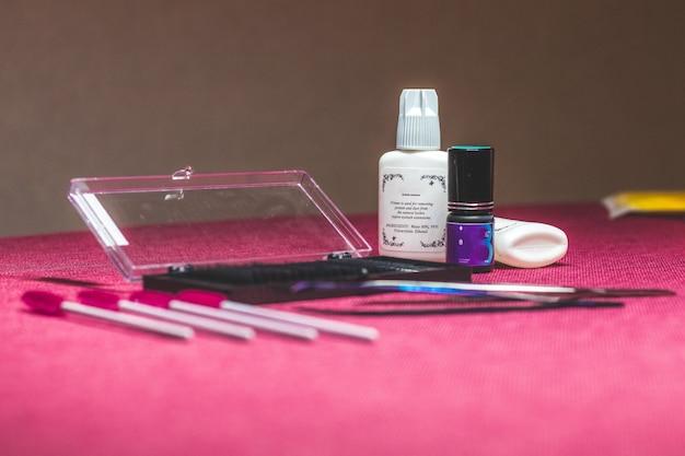 目のためのツールのセット。化粧品はまつげブラシ、マスカラ、カーラー、つけまつげで構成されています。 Premium写真