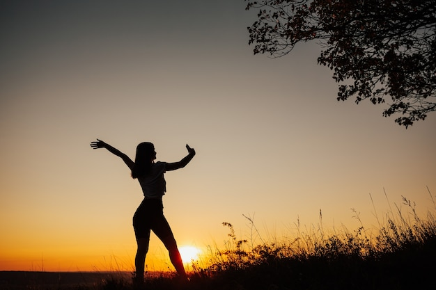 Силуэт одинокой женщины с поднятой рукой, которая делает селфи на закате. Premium Фотографии