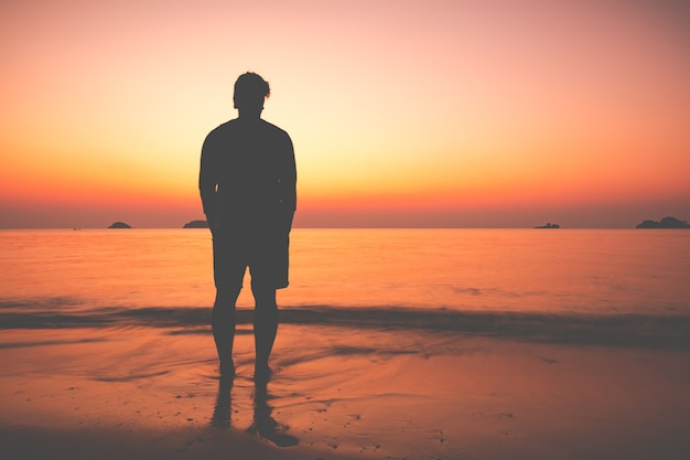 the silhouette of man sitting alone at the beach photo premium