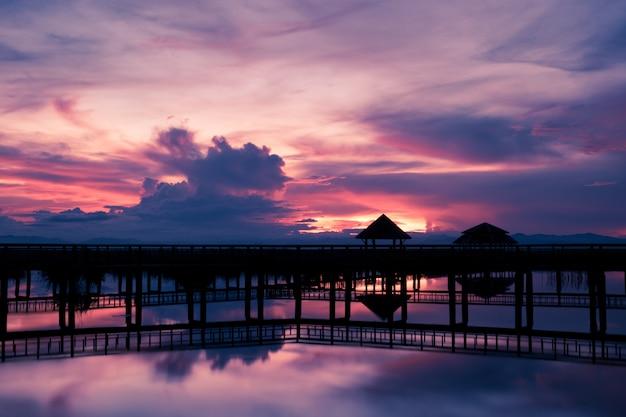Силуэт моста с красивым небом на закате, озеро лотоса на закате в национальном парке као сэм рой йот, таиланд Premium Фотографии