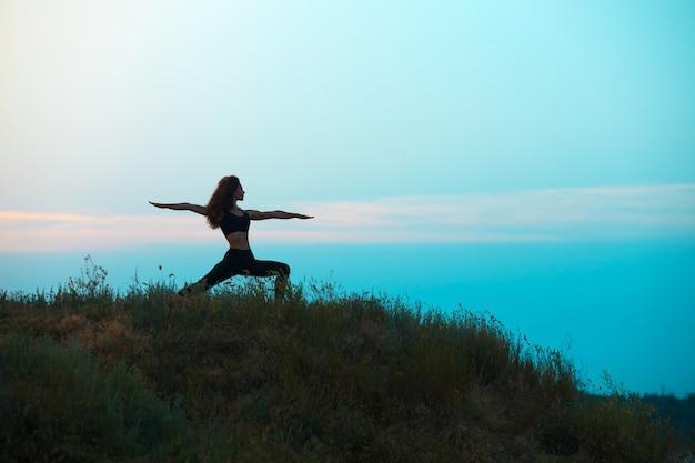 若い女性のシルエットはヨガを練習しています。 無料写真