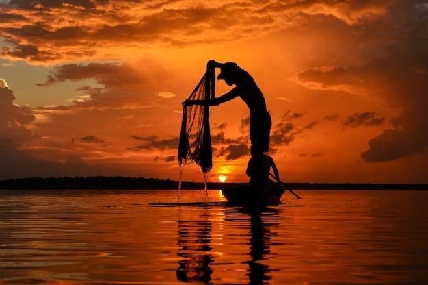 日の出、タイの中に川のsilluate漁師のボート Premium写真